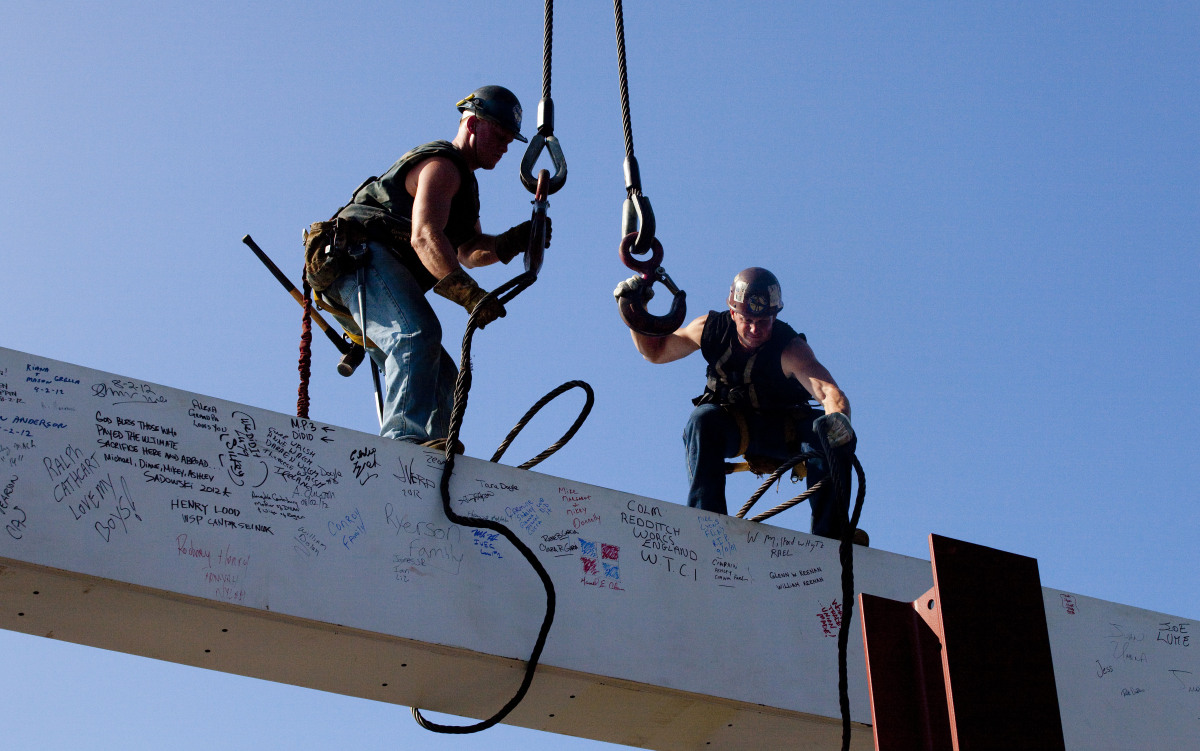 James Brady (left) installing the final steel column, signed by President Obama, Steelworkers and the NYPD in 2012.